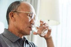 Asian Senior man drinking water. Elderly male holding transparent glass in his hand Royalty Free Stock Images
