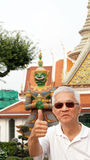Asian senior man with green giant in temple of dawn, Bangkok, Th Royalty Free Stock Photography