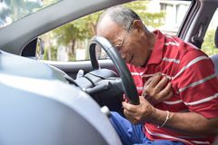 Asian Senior man having heart attack. Asian Senior man in red shirt having chest pain from heart attack while driving a car. Illness, exhausted, disease stock images
