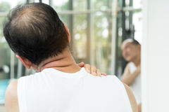 Asian senior man having pain on his shoulder and neck. Stock Photography