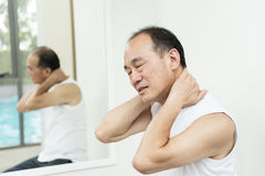 Asian senior man having pain on his shoulder and neck. copy spac Royalty Free Stock Images