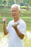 Asian senior man healthy lifestyle working out on a park. Korean Asian senior man healthy lifestyle working out on a park with a dumbbell Royalty Free Stock Photography