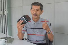 Asian senior man, Holding VR glasses with Feeling happy for modern technology. Front on the desk. there are white coffee mug and laptop computer, pen in the royalty free stock images