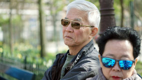 Asian senior man looking angry at his wife through sunglasses wh Stock Photo