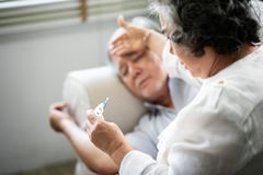 Asian Senior man lying on sofa while his wife holding and looking to thermometer stock photography
