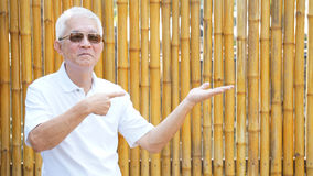 Asian senior man present product with golden bamboo background c Stock Images