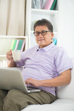 Asian Senior Man Reading Stock Image