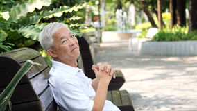 Asian senior man relaxing in the park laughing in sunshine Royalty Free Stock Photo