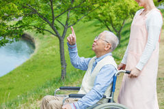 Asian senior man sitting on a wheelchair pointing Royalty Free Stock Photos