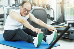 Asian senior man Stretching before workout. At the gym. copy space Stock Image