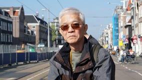 Asian senior man take a solo trip to Amsterdam waiting for tram Stock Photo