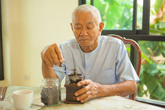 Asian senior man with vintage coffee grinder Stock Images