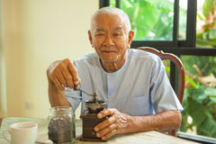 Asian senior man with vintage coffee grinder Royalty Free Stock Images