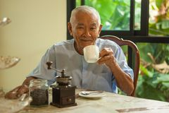 Asian senior man with vintage coffee grinder Royalty Free Stock Image