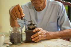 Asian senior man with vintage coffee grinder Royalty Free Stock Photography