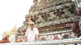 Asian senior man visiting wat pho, giants sculptures in the temp Royalty Free Stock Photos