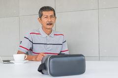Asian senior man with VR glasses for modern technology. Looking to VR glasses Thinking something, in the office stock images