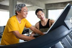 asian Senior man walking exercise on treadmill with Personal trainer workout in fitness gym . sport trainnig , retired , older ,