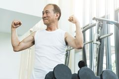 Asian senior man working out at the gym. Copy space stock photo