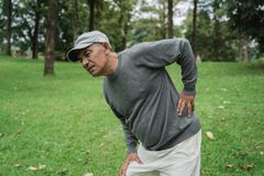 Asian senior old man having back pain. While exercising outdoor in the park stock image
