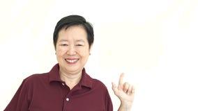 Asian senior pointing smiling on white isolate background Royalty Free Stock Photos