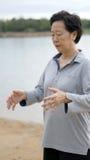Asian Senior Practice Taichi, Qi Gong exercise next to the lake royalty free stock photo