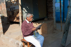 Asian senior read a newspaper outdoor at morning i Stock Photos