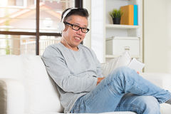 Asian senior relaxing with entertainment Stock Image