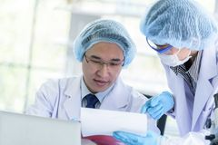 Asian senior scientist male researching and learning in a laboratory. Background beaker biology biotechnology black blue chemical chemist chemistry colorful stock photo