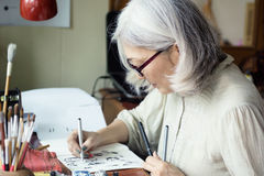 Asian senior woman artist sketching. Focus on face, blurred workspace in background. Art background, text space Royalty Free Stock Image