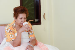 Asian Senior Woman in bedroom with tea cup. Royalty Free Stock Photos