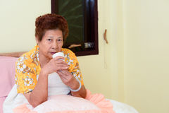 Asian Senior Woman in bedroom with tea cup. Royalty Free Stock Images
