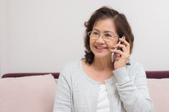 Asian senior woman cheerfully chatting with friends on mobile ph. One Royalty Free Stock Photos
