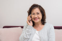 Asian senior woman cheerfully chatting with friends on mobile ph. One Stock Photos