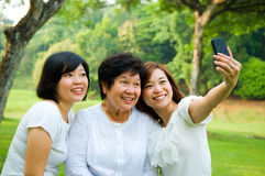 Asian senior woman and daughters. Asian senior women and daughters taking picture with mobile phone Stock Images