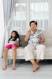 Asian senior woman eating popcorn. Asian senior women eating popcorn with her grandchild while watching TV at home, selective focus Royalty Free Stock Photos