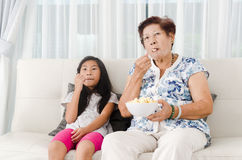 Asian senior woman eating popcorn with her grandchild Stock Image