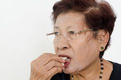 Asian senior woman eating popcorn. While watching TV, at home Stock Photography