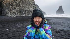 Asian senior woman drean trip travel to Icealand, black beach. Asian senior woman having drean trip travel to Icealand, black beach Stock Photography
