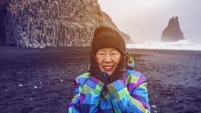 Asian senior woman drean trip travel to Icealand, black beach. Asian senior woman having drean trip travel to Icealand, black beach Royalty Free Stock Photo