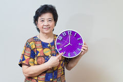 Asian senior woman holding purple clock in studio shot, specialt Royalty Free Stock Photos