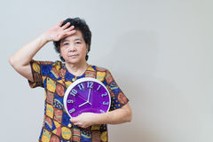 Asian senior woman holding purple clock in studio shot, specialt Royalty Free Stock Image