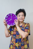 Asian senior woman holding purple clock in studio shot, specialt Stock Images