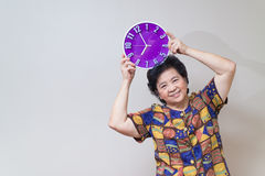 Asian senior woman holding purple clock in studio shot, specialt Stock Image