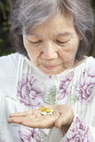 Asian Senior Woman Looking At Pills Royalty Free Stock Photos