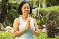 Asian senior woman meditating for yoga outside Stock Image