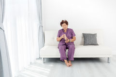 Asian senior woman open brown book. And sitting on sofa near window at home Royalty Free Stock Photos