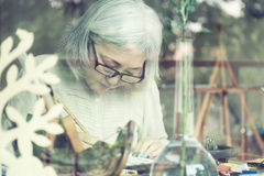 Free Asian Senior Woman Painting At Her Home Studio Royalty Free Stock Image - 73887596