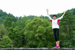 Asian senior woman raise up hand in park. Asian senior woman raise up hand with joy and happiness in park Royalty Free Stock Photography