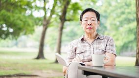 Asian senior woman reading book drinking coffee in sunny park, g Stock Image
